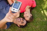 Two friends using a camera while lying side by side