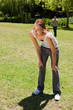woman bending over while man is walking in the background