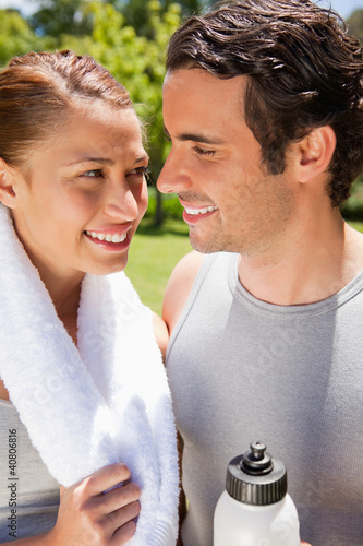 Smiling woman holding a towel while looking at a man