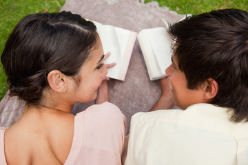 Rear view of two friends looking at each other while reading on