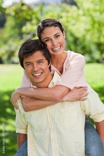 Woman looking ahead while her friend is carrying her on his back