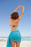 Rear view of a beautiful woman in beachwear raising her arms wit