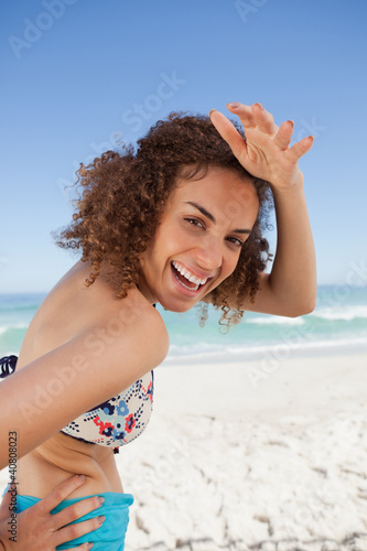 Young smiling woman placing her hand on her forehead to look at