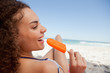 Young smiling woman holding a popsicle in front of the sea