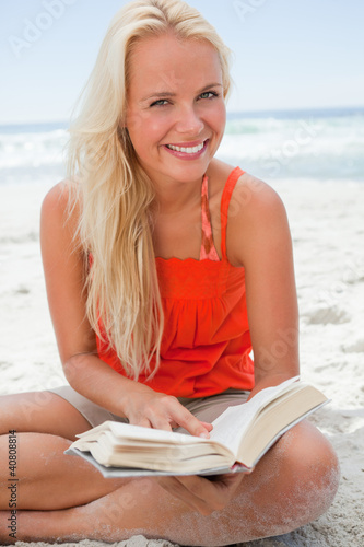 Young blonde woman looking at the camera while smiling and readi