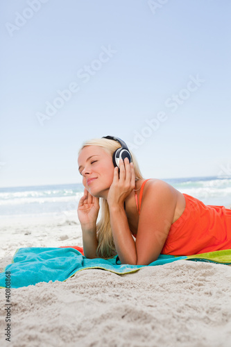 Thoughtful young woman lying on the beach while listening to mus