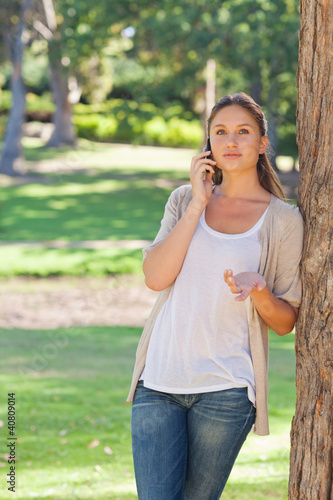Woman talking on her phone while leaning against a tree