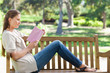 Side view of a woman reading a novel on a park bench