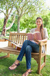 Smiling woman sitting on a bench with a guitar and a book