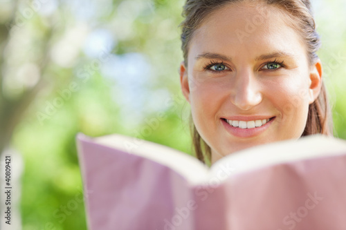 Smiling woman reading a book in the park