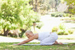 Side view of a woman doing stretches on the lawn