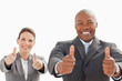 Businessman and woman with their thumbs up