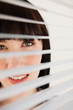 A woman looking forward through her blinds without moving them