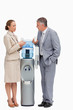 People in suit talking next to the water dispenser