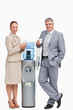 Portrait of smiling business people next to the water dispenser
