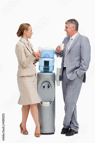 Business people talking next to the water dispenser
