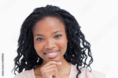 Head shot of a smiling young woman resting her head on her hand