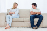 A couple sit at the two ends of the couch with their arms folded