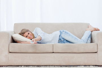 A smiling woman lying on a couch is holding a TV remote control