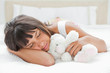 Cute young woman sleeping with a teddy bear