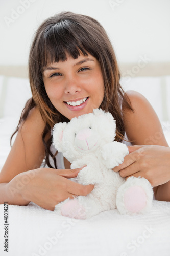 Portrait of a young woman playing with a teddy bear
