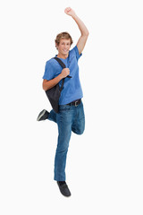 Young blond man jumping with a backpack