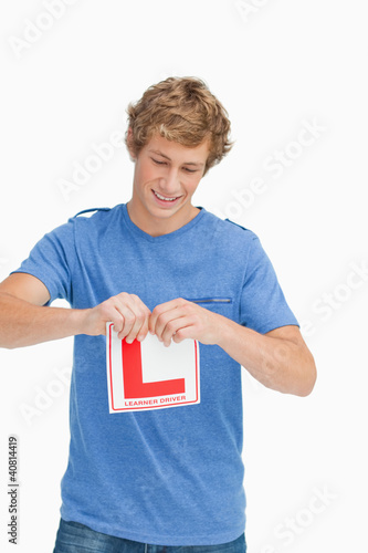 Young man ripping a learner driver sign