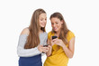 Two young women smiling while looking their cellphones