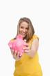 Young smiling woman tending a piggy-bank