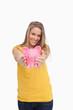 Young blond woman tending a piggy-bank