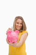Young blond woman putting money into a piggy-bank