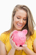 Close-up of a blond woman looking a piggy-bank
