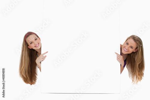 Portrait of wo long hair women back of a blank sign