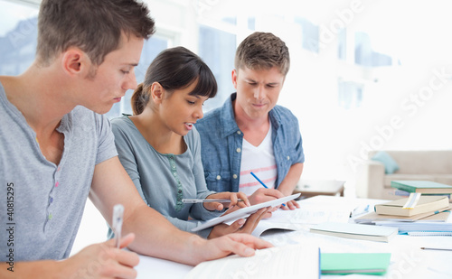 Side view of three students studying