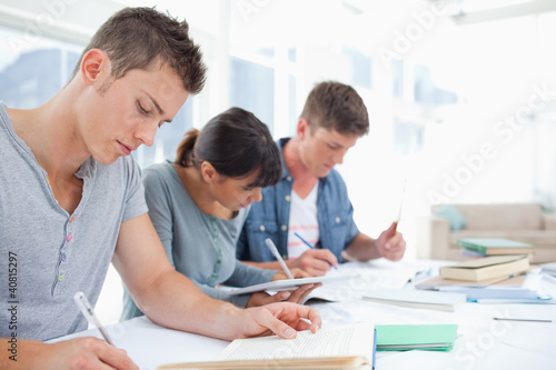 Side view of three students quietly working together