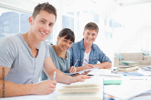 Three smiling students doing homework as they look into the came