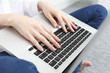 女性の手とパソコン
