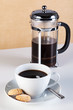 Cup of coffee with cafetiere and amaretti biscuits