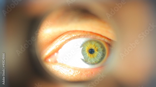 Mans eye looking through a blured hole