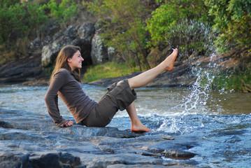 Fröhliche junge Frau spritzt Wasser mit dem Fuß