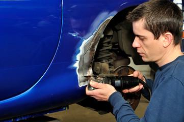 Car body worker cutting metal.