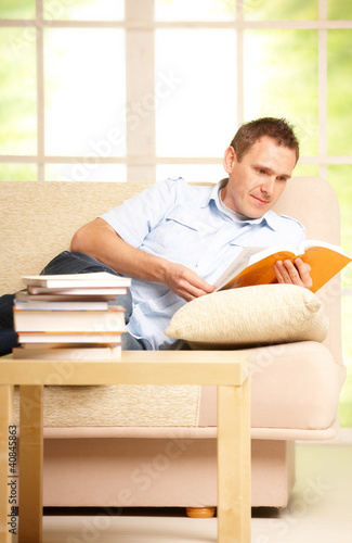 Man reading book in room