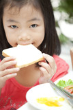 young pretty girl with ponytail eating bread poster