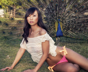 Exotic Asian model posing with peacock