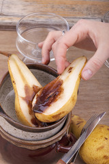 hand holding fresh halved pear with melted chocolate