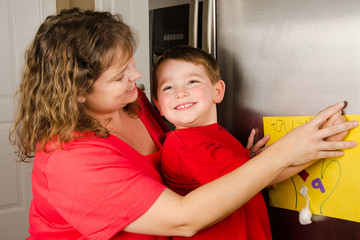 Mother and child putting up boy's art on family refrigerator