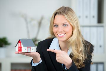 makler zeigt mit dem finger auf  miniaturhaus