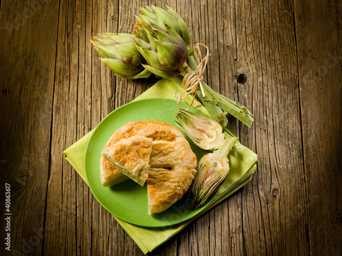 vegetarian quiche with artichoke on wood background