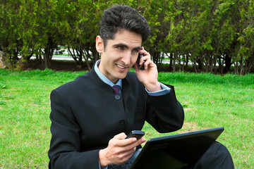 Young man with cell phones and laptop.