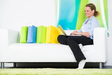 frau sitzt mit ihren einkaufstaschen auf dem sofa